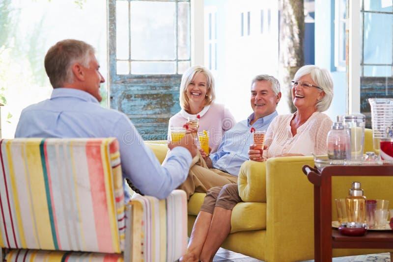 Grupo de amigos em casa que relaxam na sala de estar com bebidas frias fotos de stock