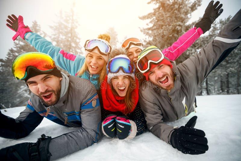 Grupo de amigos em feriados de inverno - esquiadores que encontram-se na neve e no h imagens de stock