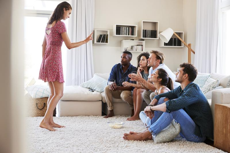 Grupo de amigos en casa que se divierten que juega charadas juntas foto de archivo libre de regalías