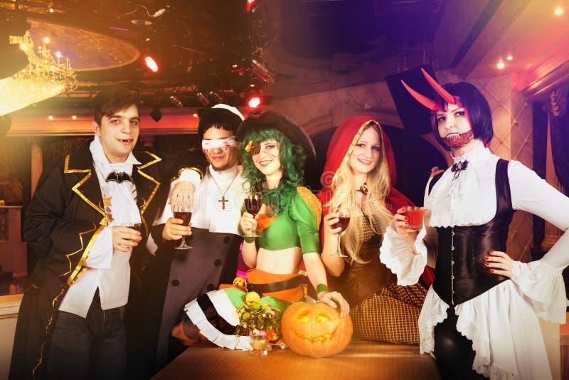 Grupo de amigos en el partido de Halloween en trajes foto de archivo