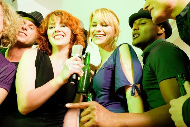 Grupo de amigos en el partido del Karaoke foto de archivo