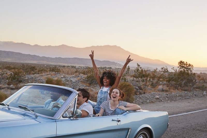Grupo de amigos en el viaje por carretera que conduce el coche convertible clásico imagenes de archivo