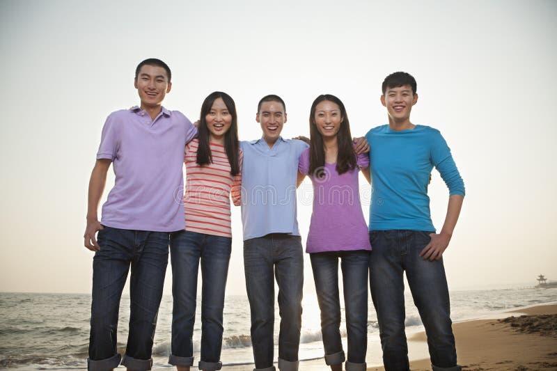 Grupo de amigos en la playa foto de archivo