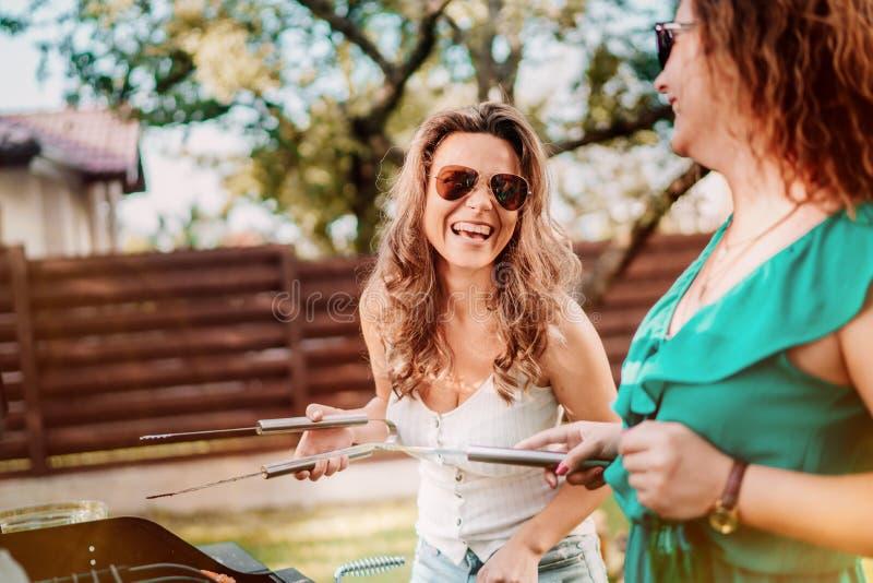 Grupo de amigos en las vacaciones que comen cervezas y que cocinan en barbacoa del jardín Forma de vida, concepto del ocio imagen de archivo