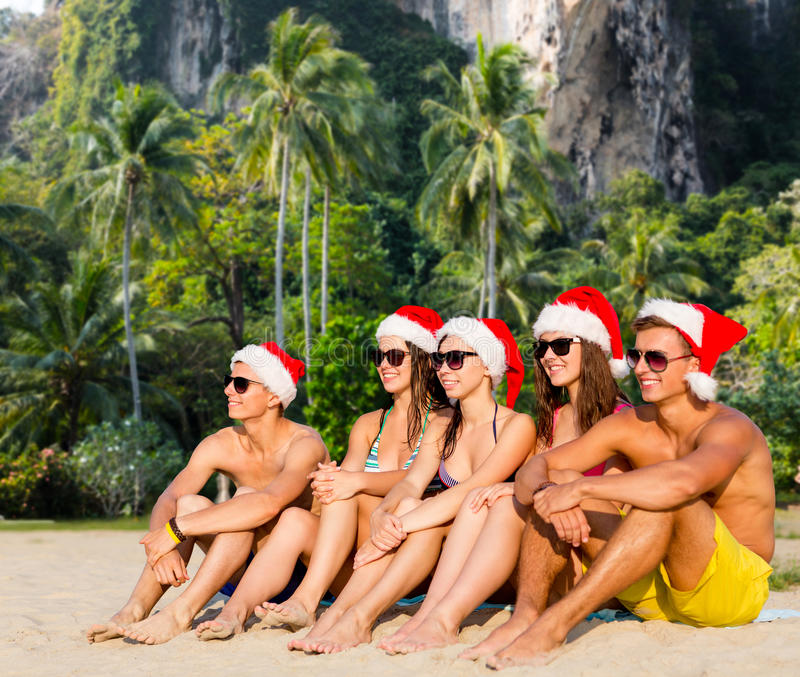 Grupo de amigos en sombreros del ayudante de santa en la playa imágenes de archivo libres de regalías