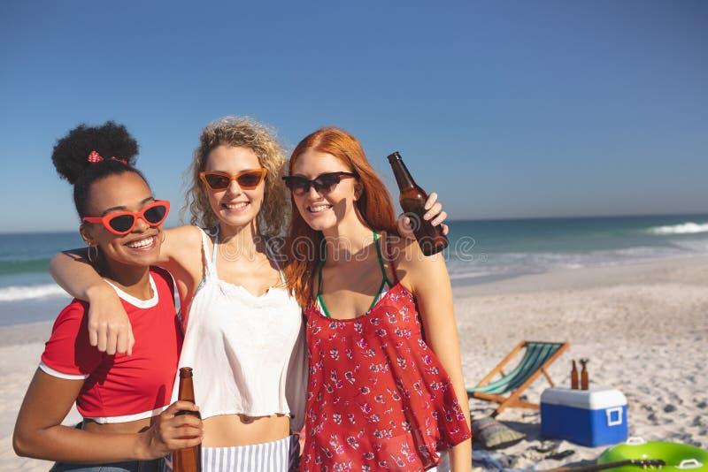 Grupo de amigos fêmeas que estão junto na praia foto de stock
