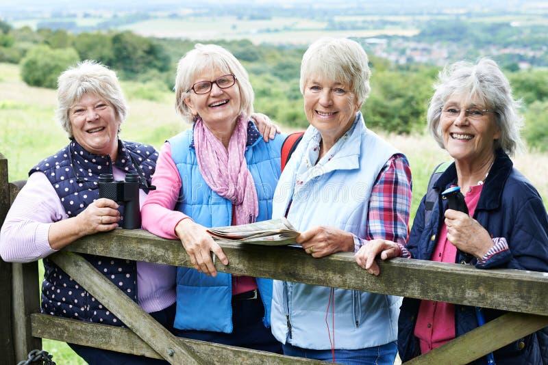 Grupo de amigos fêmeas superiores que caminham no campo imagem de stock royalty free
