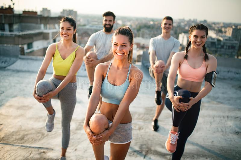 Grupo de amigos felices jovenes de la gente que ejercitan al aire libre en la puesta del sol imagen de archivo