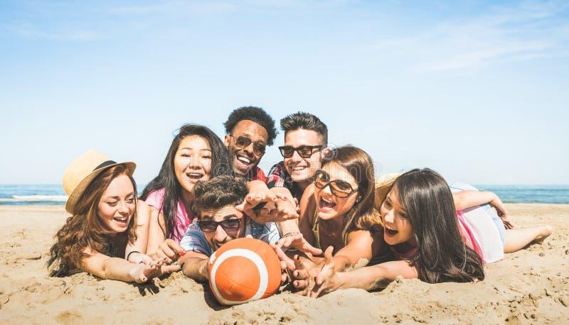 Grupo de amigos felices multirraciales que se divierten que juega el beac del deporte imágenes de archivo libres de regalías