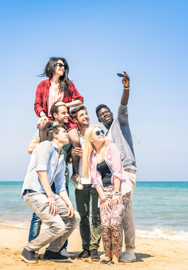 Grupo de amigos felices multirraciales que toman un selfie imagenes de archivo