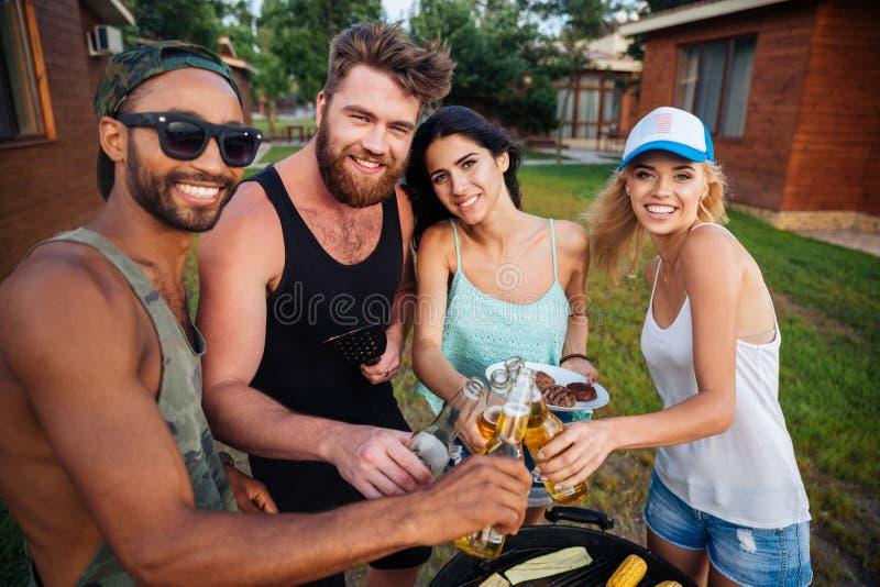 Grupo de amigos felices que beben la cerveza y que tienen barbacoa al aire libre imagen de archivo libre de regalías