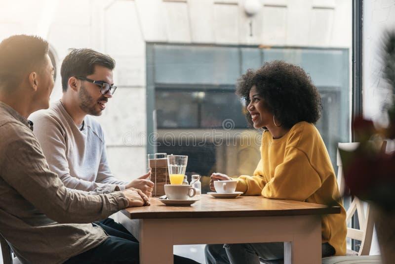 Grupo de amigos felices que charlan en la cafetería foto de archivo