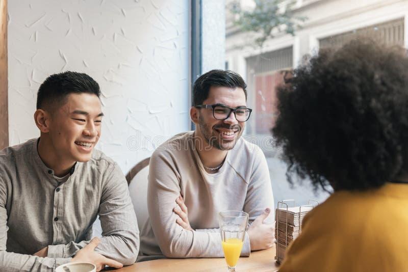 Grupo de amigos felices que charlan en la cafetería fotos de archivo libres de regalías