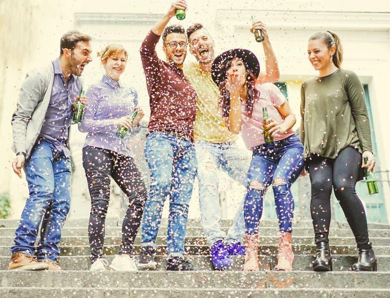 Grupo de amigos felices que comen cervezas de consumición de una fiesta en la calle mientras que está cayendo el confeti abajo imagenes de archivo
