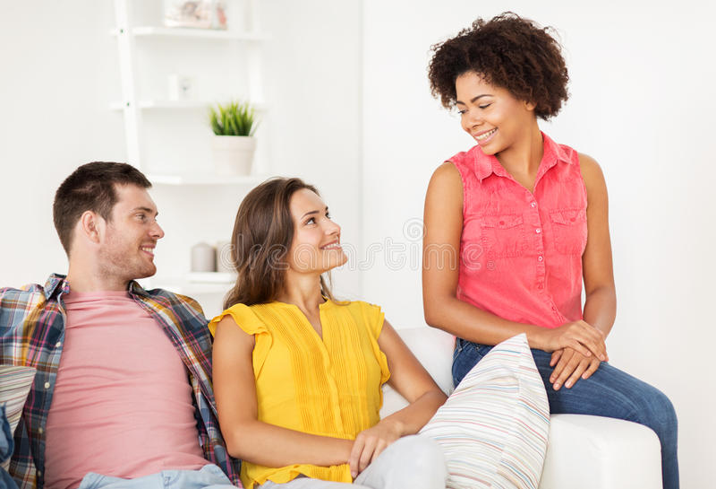 Grupo de amigos felices que hablan en casa fotografía de archivo libre de regalías