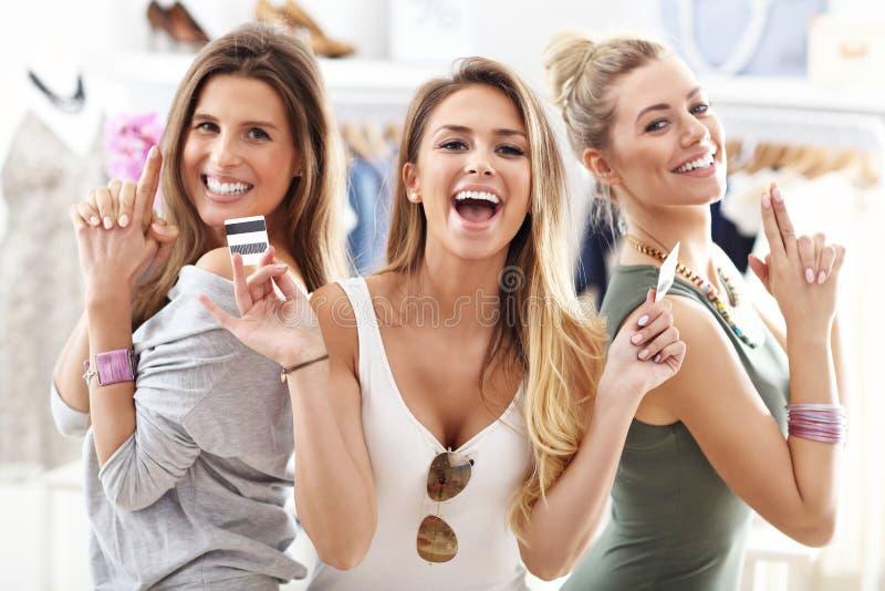 Grupo de amigos felices que hacen compras en tienda imagenes de archivo