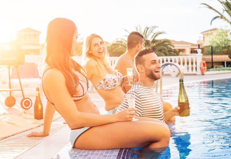 Grupo de amigos felices que hacen a una fiesta en la piscina en la puesta del sol - gente joven que ríe y que come el champán de  imagen de archivo