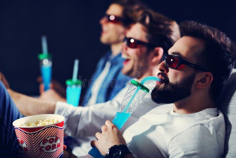Grupo de amigos felices que se sientan en película del reloj del cine y que comen las palomitas fotos de archivo