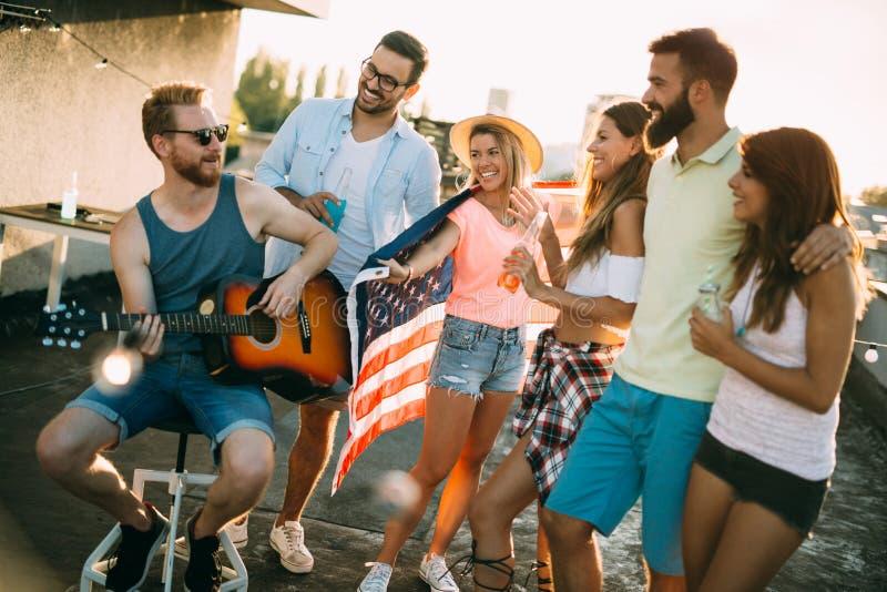 Grupo de amigos felices que tienen partido en tejado fotos de archivo libres de regalías