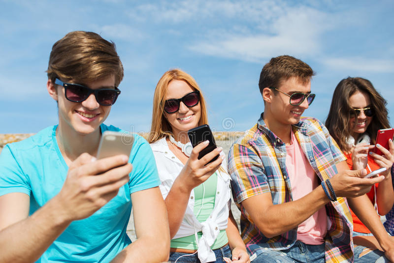 Grupo de amigos felizes com smartphones fora fotografia de stock