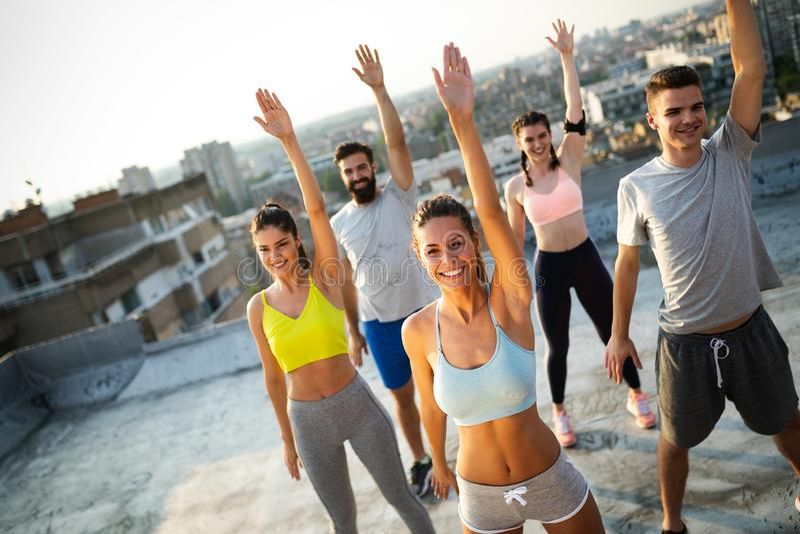 Grupo de amigos felizes novos dos povos que exercitam fora no por do sol foto de stock royalty free