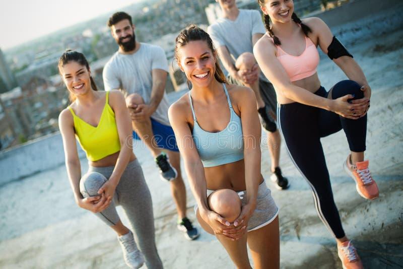 Grupo de amigos felizes novos dos povos que exercitam fora no por do sol foto de stock