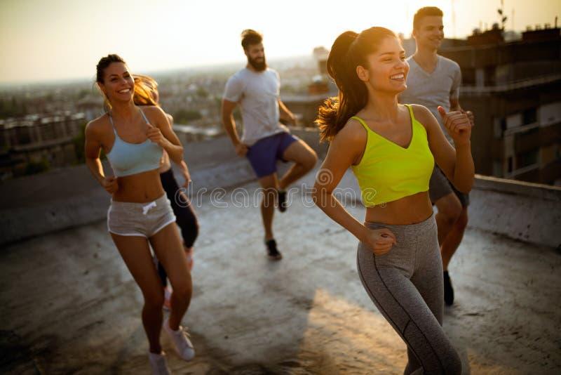 Grupo de amigos felizes novos dos povos que exercitam fora no por do sol fotos de stock royalty free