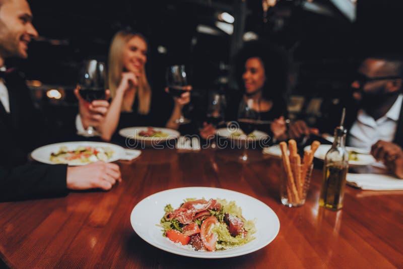 Grupo de amigos felizes que encontram e que têm o jantar imagem de stock royalty free