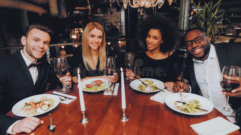Grupo de amigos felizes que encontram e que têm o jantar foto de stock royalty free