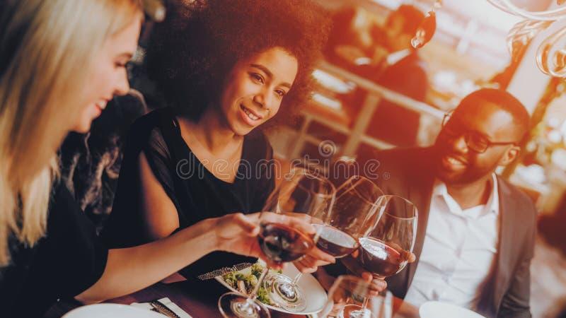 Grupo de amigos felizes que encontram e que têm o jantar imagens de stock