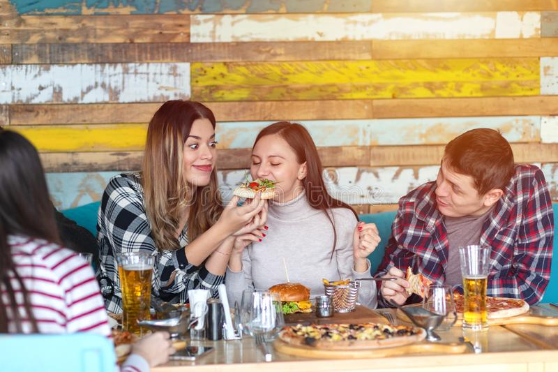 Grupo de amigos felizes que têm o almoço no restaurante, jovens mulheres que compartilham de uma fatia de pizza ao sorrir e ao ap fotos de stock