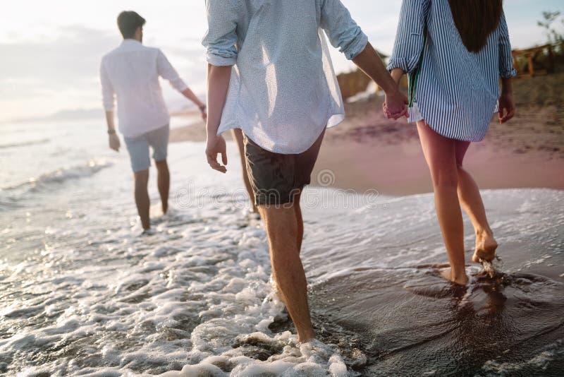 Grupo de amigos felizes que t?m o divertimento que anda abaixo da praia no por do sol fotografia de stock