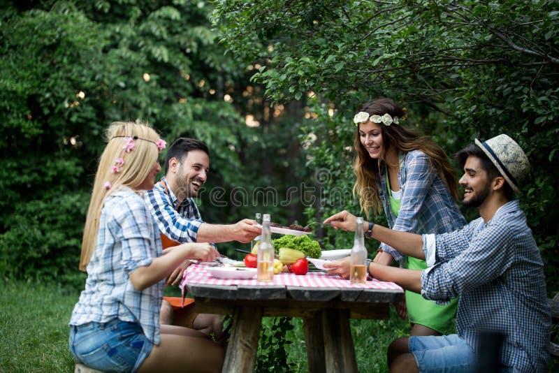 Grupo de amigos felizes que t?m o assado exterior que ri junto imagem de stock