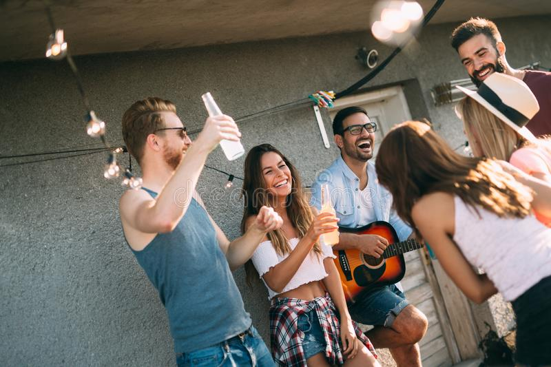 Grupo de amigos felizes que t?m o partido no telhado fotos de stock