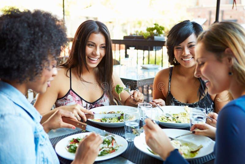 Grupo de amigos femeninos que disfrutan de la comida en el restaurante al aire libre foto de archivo libre de regalías