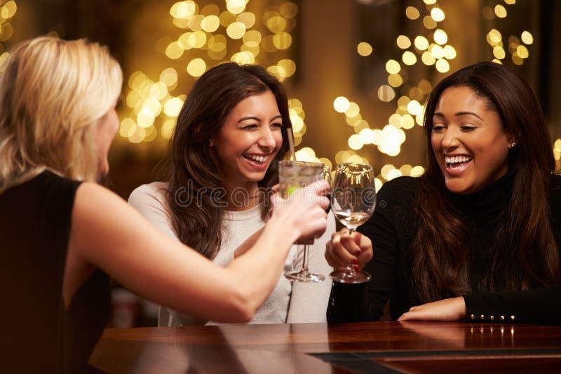 Grupo de amigos femeninos que gozan igualando bebidas en barra fotografía de archivo