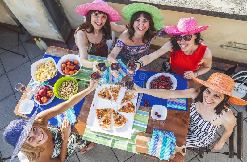 Grupo de amigos femeninos que llevan los sombreros coloridos que tuesta con el vino tinto para celebrar en una terraza fotografía de archivo