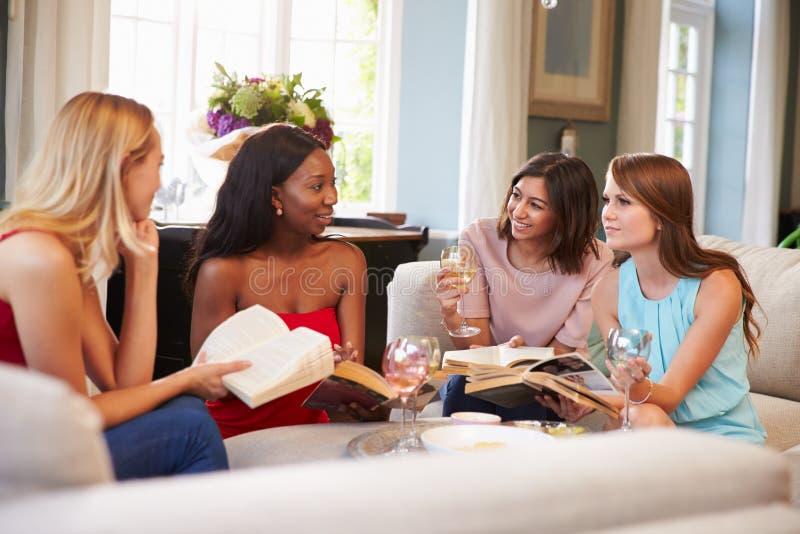 Grupo de amigos femeninos que participan en círculo de lectores en casa fotografía de archivo libre de regalías