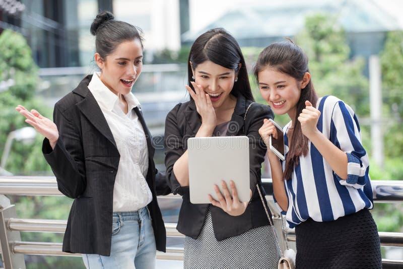 grupo de amigos hermosos de las mujeres jovenes que usan un teléfono elegante y riendo aire libre negocio emocionante de tres muc foto de archivo libre de regalías