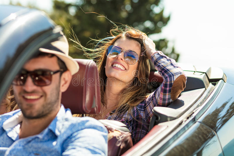 Grupo de amigos jovenes alegres que conducen el coche y que sonríen en verano fotos de archivo libres de regalías