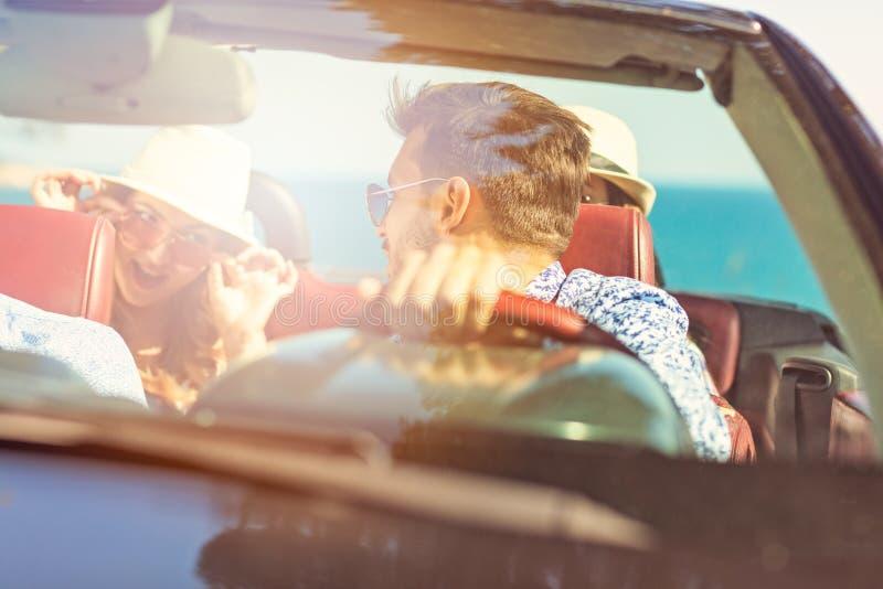 Grupo de amigos jovenes alegres que conducen el coche y que sonríen en verano imagen de archivo