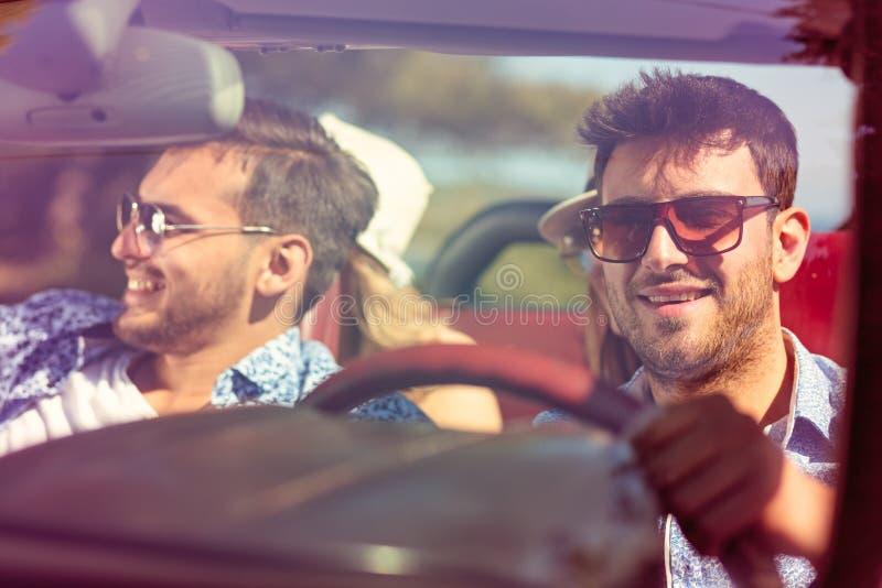 Grupo de amigos jovenes alegres que conducen el coche y que sonríen en verano fotos de archivo