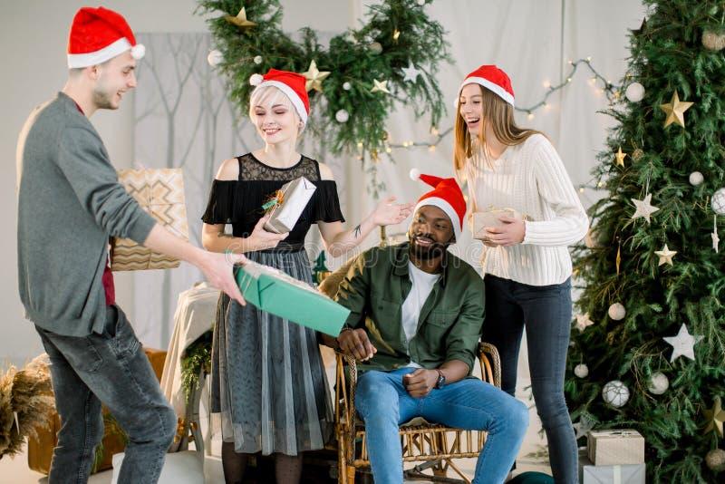 Grupo de amigos jovenes cerca del árbol de navidad agradable adornado, intercambiando regalos de Navidad y divirtiéndose fotos de archivo libres de regalías