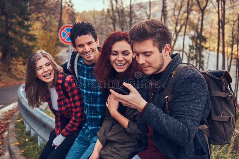 Grupo de amigos jovenes con las mochilas que se sientan en la barandilla cerca del camino y que usan smartphone Viaje, alza, conc fotos de archivo