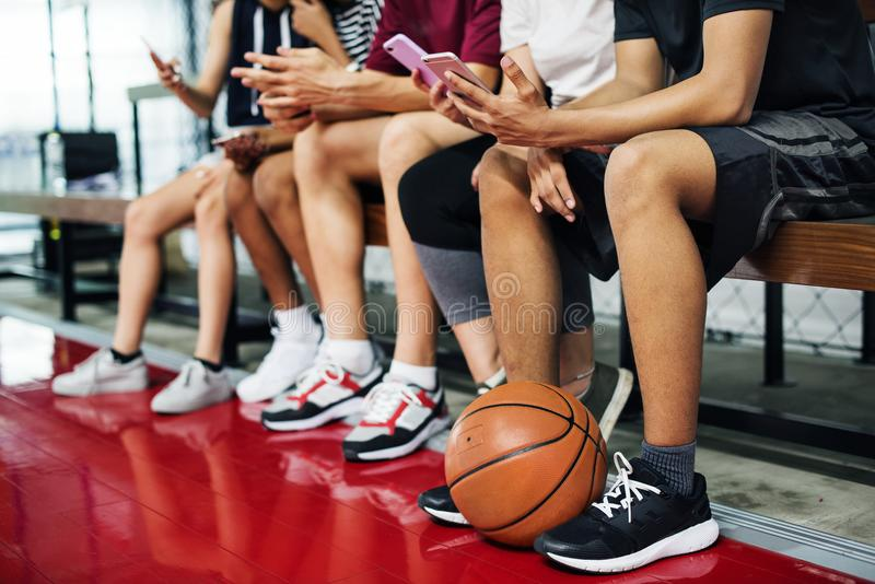 Grupo de amigos jovenes del adolescente en una cancha de básquet que se relaja usando concepto del apego del smartphone fotos de archivo
