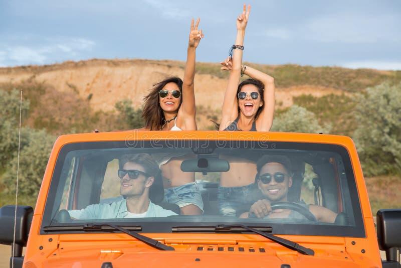 Grupo de amigos jovenes emocionados que se colocan en un coche con las manos aumentadas imágenes de archivo libres de regalías