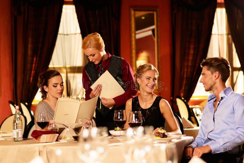 Grupo de amigos jovenes en restaurante imagen de archivo