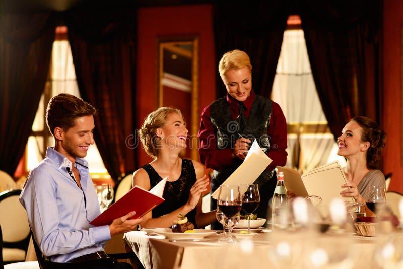 Grupo de amigos jovenes en restaurante imagenes de archivo