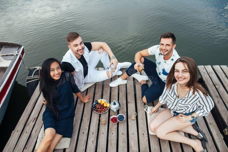 Grupo de amigos jovenes felices que se relajan en el embarcadero de madera del río imagenes de archivo