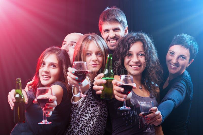 Grupo de amigos jovenes hermosos en el club del disco imagen de archivo libre de regalías